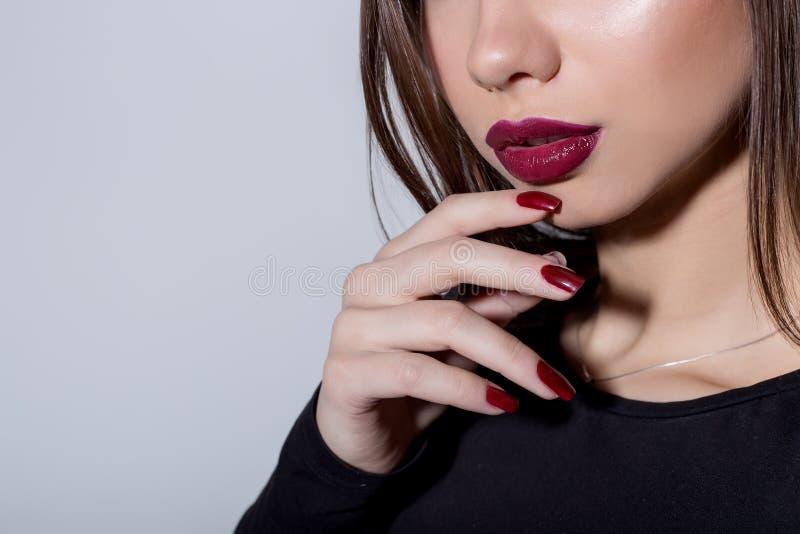 Il ritratto alla moda di bella giovane donna sexy con il rossetto rosso di modo luminoso e la sera luminosa preparano su un bianc immagini stock
