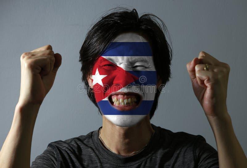Il ritratto allegro di un uomo con la bandiera di Cuba ha dipinto sul suo fronte su fondo grigio immagine stock