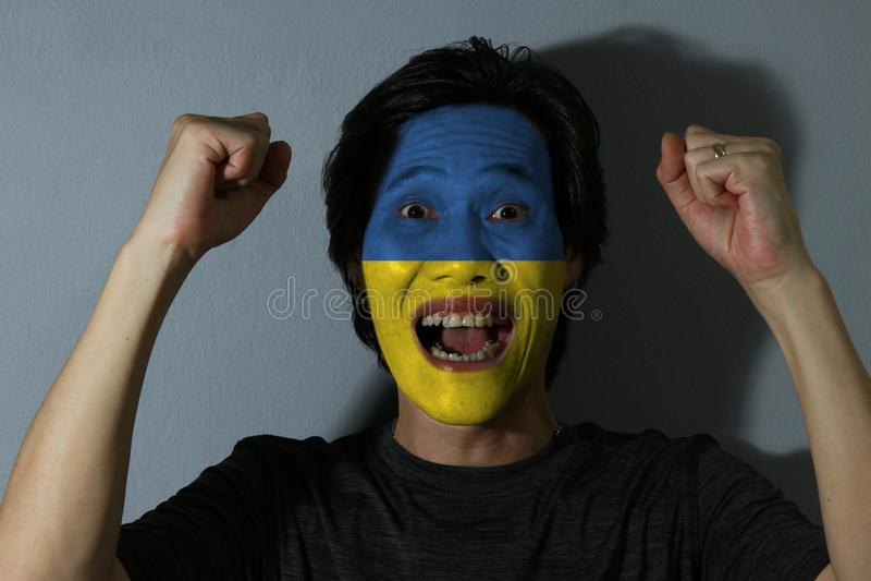 Il ritratto allegro di un uomo con la bandiera dell'Ucraina ha dipinto sul suo fronte su fondo grigio Il concetto dello sport o d immagine stock libera da diritti