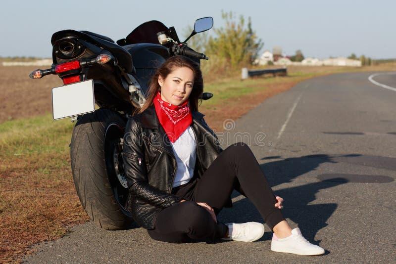 Il ritratto alto vicino del motociclista femminile spensierato indossa i vestiti neri e gli istruttori bianchi, si siede vicino a immagini stock libere da diritti