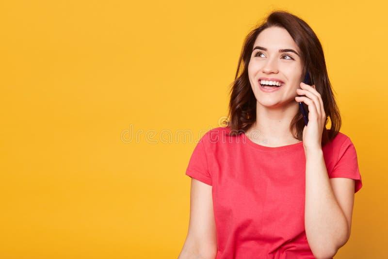 Il ritratto alto vicino della ragazza in maglietta rossa, guarda da parte con espressione facciale premurosa, parla sul telefono  fotografie stock libere da diritti