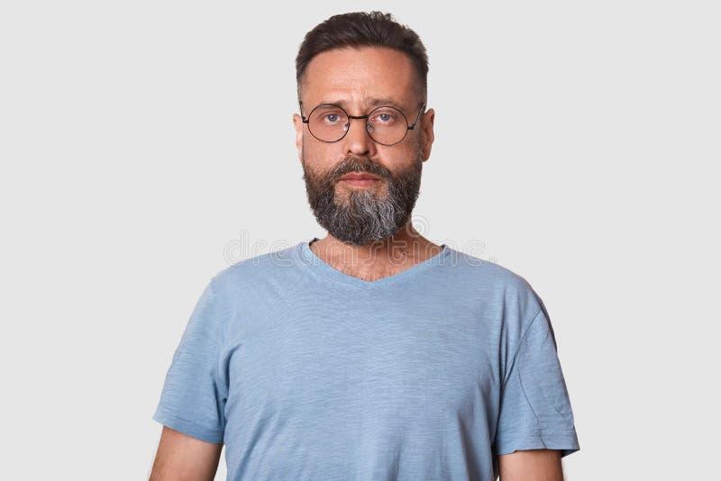 Il ritratto alto vicino di giovane maschio serio moro con la barba, uomo esamina con confidenza la macchina fotografica, magliett immagine stock