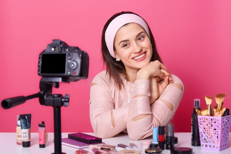 Il ritratto alto vicino di giovane vlogger femminile caucasico sveglio, ha conversazione online con i suoi seguaci, sguardi alla  immagini stock