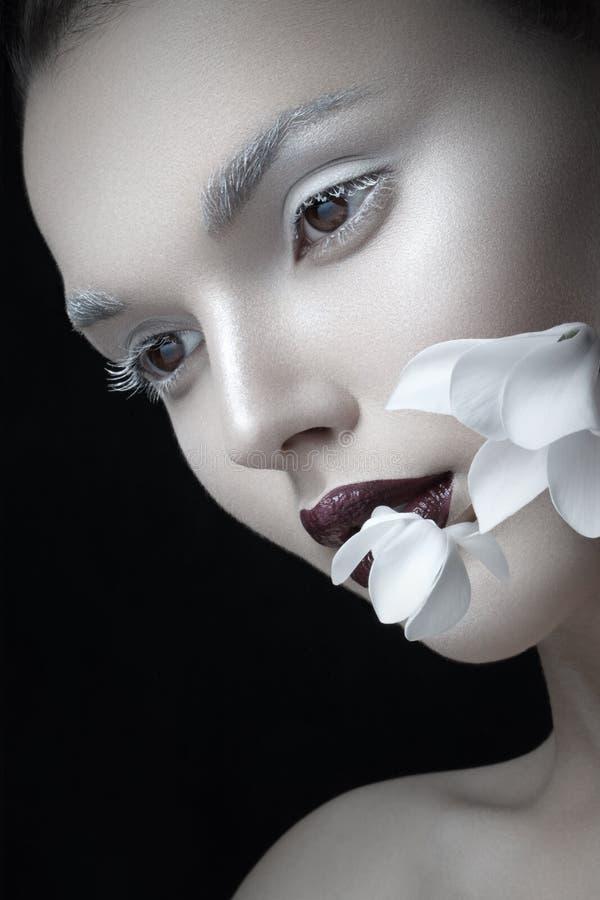 Il ritratto alto vicino di modo, compone le labbra di Borgogna ed artistiche, vicino al fiore del fronte, isolato su un fondo ner immagine stock libera da diritti