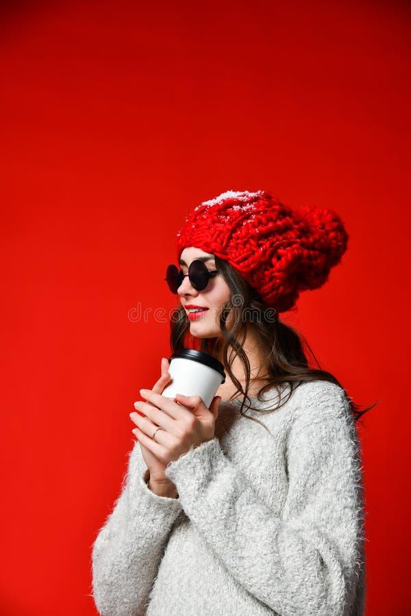 Il ritratto alto vicino di una ragazza sorridente nella tenuta del cappello porta via la tazza di caffè immagine stock