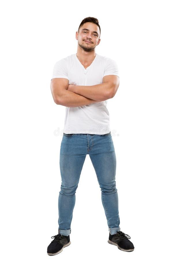 Il ritratto completo del corpo dell'uomo su fondo bianco, il ragazzo in maglietta ed i jeans, armi hanno piegato immagine stock libera da diritti