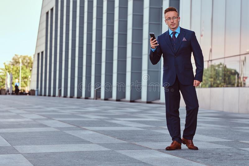 Il ritratto completo del corpo di un uomo d'affari sicuro ha vestito nelle tenute eleganti di un vestito un telefono mentre stava fotografia stock