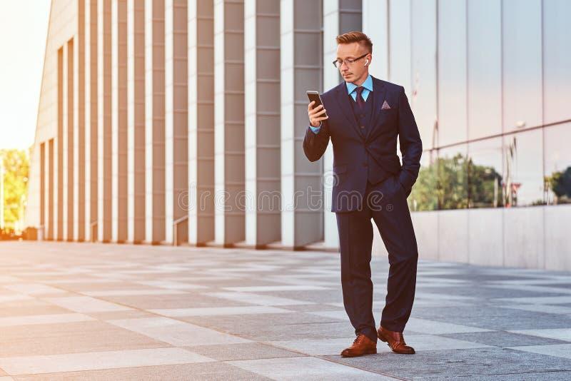 Il ritratto completo del corpo di un uomo d'affari sicuro si è vestito in vestito elegante facendo uso di un telefono mentre stav fotografia stock libera da diritti