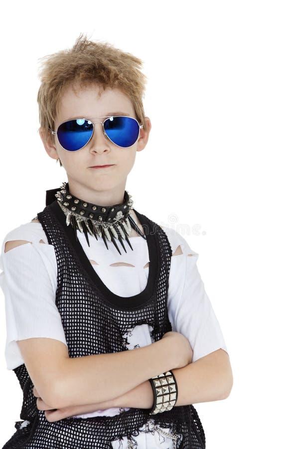 Il ritratto degli occhiali da sole d'uso del ragazzo pre-teenager punk con le armi ha attraversato il fondo bianco fotografie stock libere da diritti