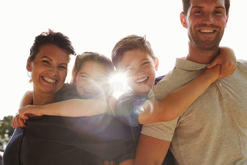 Il ritratto dei genitori che danno i bambini trasporta sulle spalle in giardino fotografia stock
