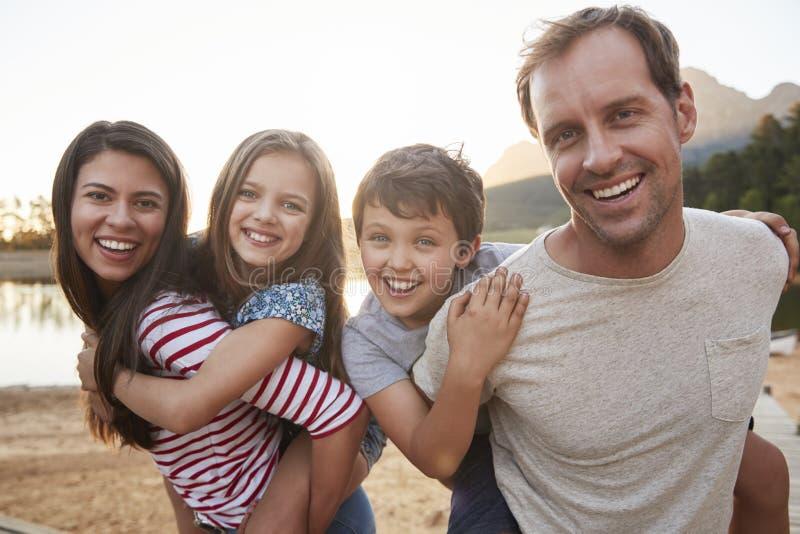 Il ritratto dei genitori che danno i bambini trasporta sulle spalle il giro in Countrysid immagini stock