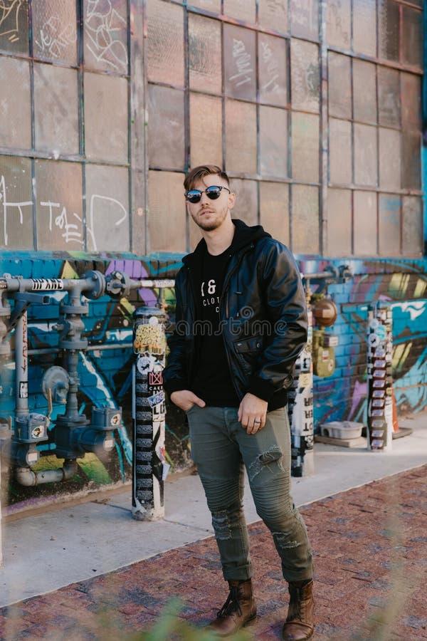 Il ritratto dei pantaloni a vita bassa moderni Guy Standing Alone del giovane in via urbana ha riguardato l'esterno variopinto de fotografia stock