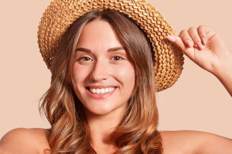 Il ritratto del cappello di paglia d'uso della donna allegra graziosa, sembrare femminile attraente sorridente direttamente alla  immagini stock libere da diritti