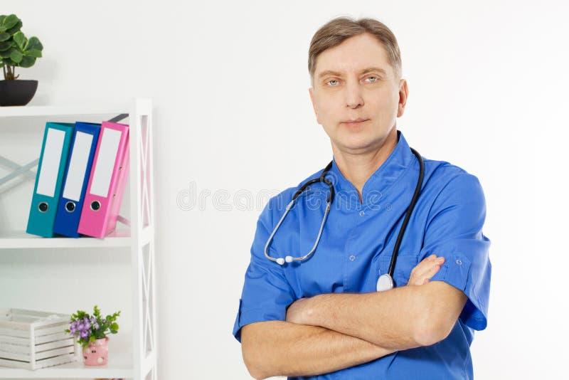 Il ritratto del dottore maturo sicuro Looking At Camera ha isolato sul fondo medico dell'ufficio immagini stock libere da diritti