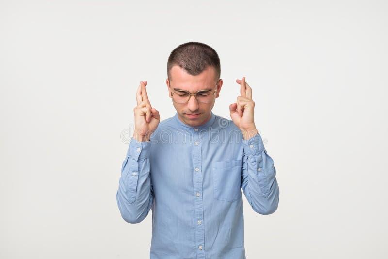 Il ritratto del giovane ispanico in dita blu della tenuta della camicia ha attraversato per buona fortuna fotografia stock libera da diritti