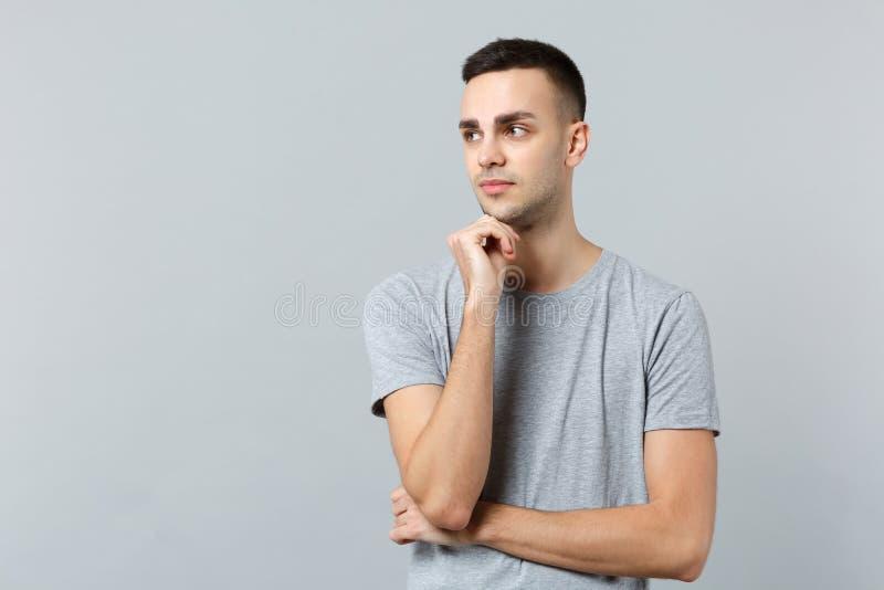 Il ritratto del giovane pensieroso in abbigliamento casual che guarda da parte ed ha messo il puntello della mano su sul mento is fotografia stock libera da diritti