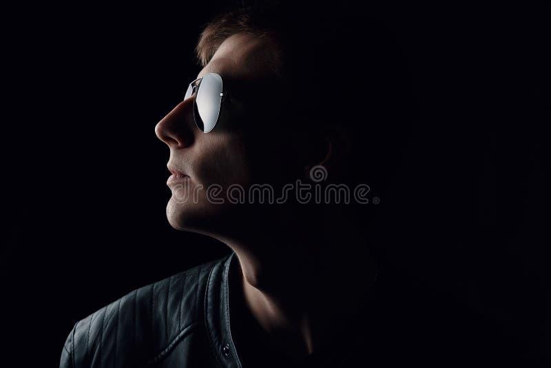 Il ritratto del giovane Primo piano del giovane serio in bomber nero ed occhiali da sole su fondo scuro fotografia stock