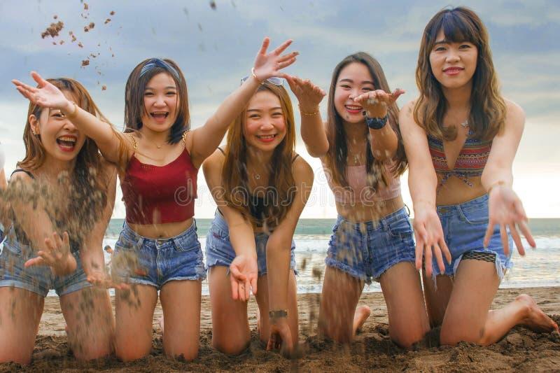 Il ritratto del gruppo felice e allegro di giovani donne coreane e cinesi asiatiche, ragazze che giocano con la sabbia inginocchi immagine stock libera da diritti