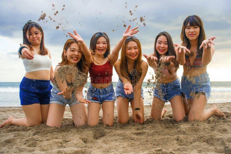 Il ritratto del gruppo felice e allegro di giovani donne coreane e cinesi asiatiche, ragazze che giocano con la sabbia inginocchi fotografia stock