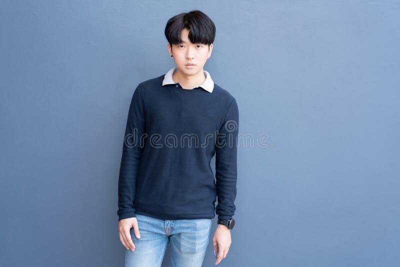 Il ritratto del maglione blu d'uso alla moda dei giovani capelli freschi adolescenti asiatici indica lo spazio sul fondo blu dell fotografia stock libera da diritti