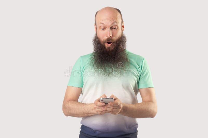 Il ritratto del mezzo colpito ha invecchiato l'uomo barbuto calvo che esamina l'esposizione mobile dello Smart Phone con il front fotografie stock libere da diritti