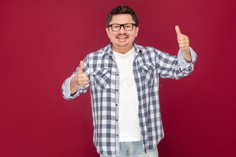Il ritratto del mezzo emozionante felice ha invecchiato l'uomo di affari nella condizione a quadretti casuale degli occhiali e de fotografie stock libere da diritti