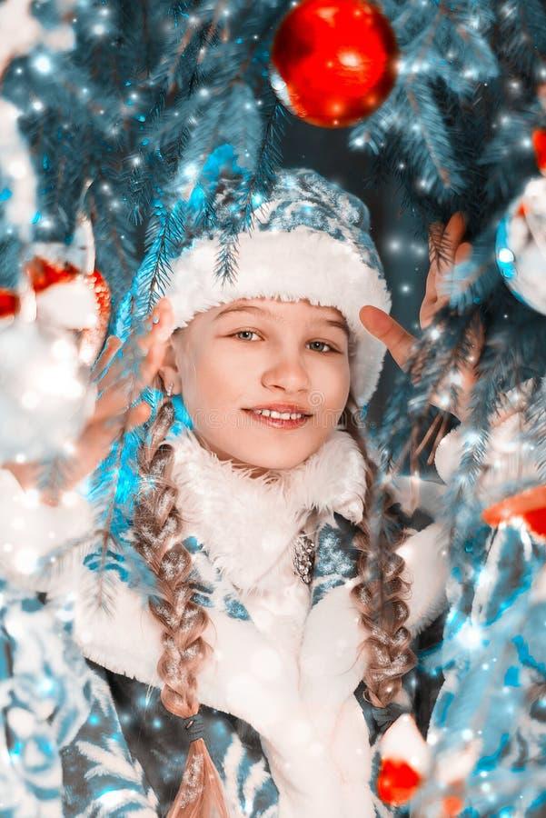 Il ritratto del nuovo anno della ragazza della neve Bella bambina vicino all'albero del nuovo anno con i regali ed i giocattoli fotografia stock libera da diritti