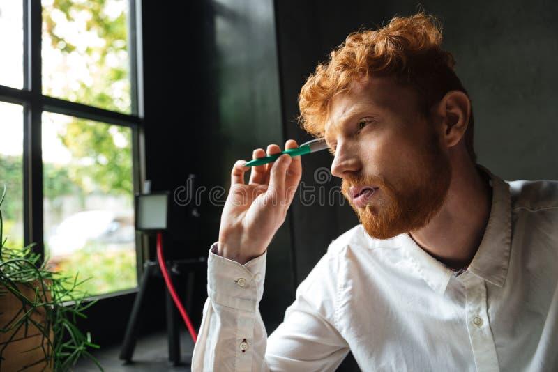 Il ritratto del primo piano dei giovani ha concentrato l'uomo barbuto del readhead, uff immagine stock
