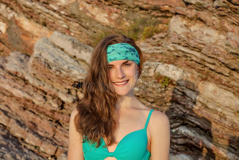 Il ritratto del primo piano dell'adolescente sta portando un bikini sul fondo della roccia al tramonto fotografie stock