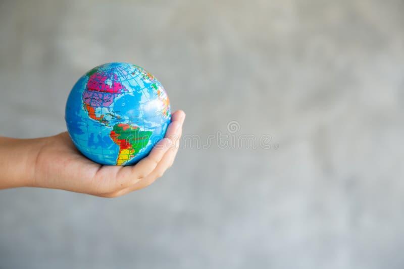 Il ritratto del primo piano della donna sta giudicando globale in sue mani su fondo grigio Salvo il pianeta ed il viaggio concett immagine stock libera da diritti