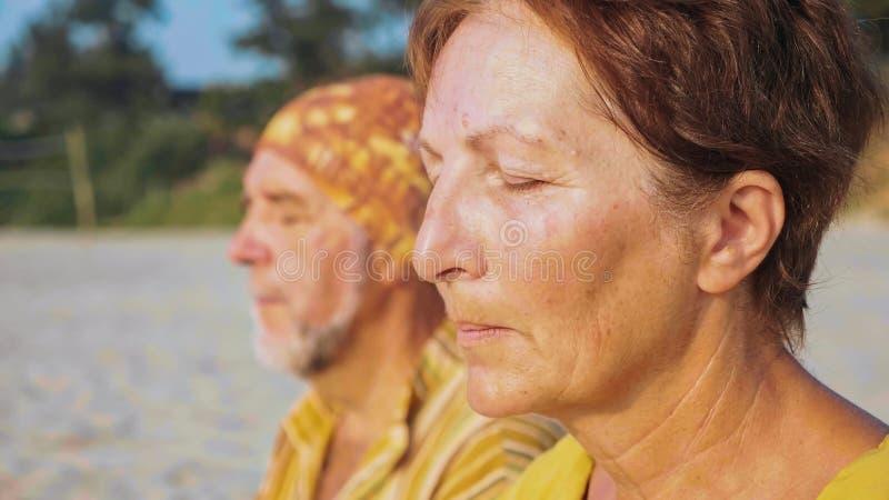Il ritratto del primo piano delle coppie senior si siede e meditando insieme su spiaggia sabbiosa immagini stock libere da diritti