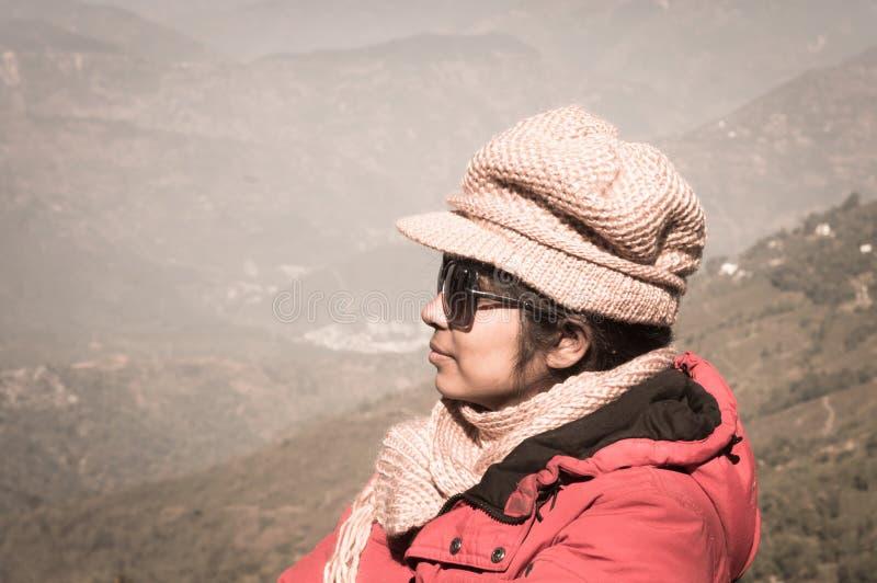 Il ritratto del primo piano di bella donna asiatica alla moda in vestiti dell'inverno, sta lateralmente su una montagna della nev fotografia stock libera da diritti