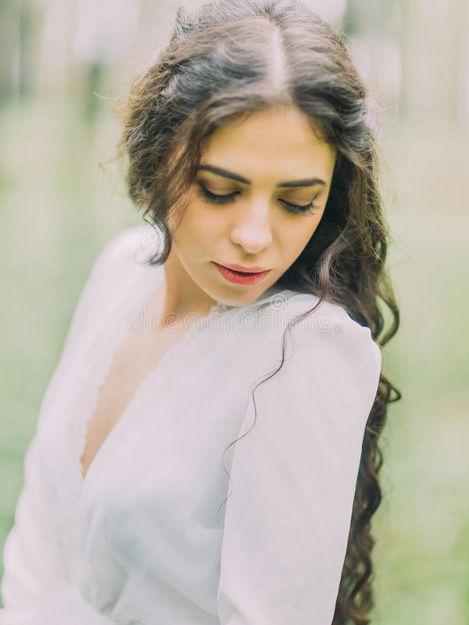 Il ritratto del primo piano di bella donna nel vestito da sposa bianco che esamina la terra nella foresta verde immagini stock