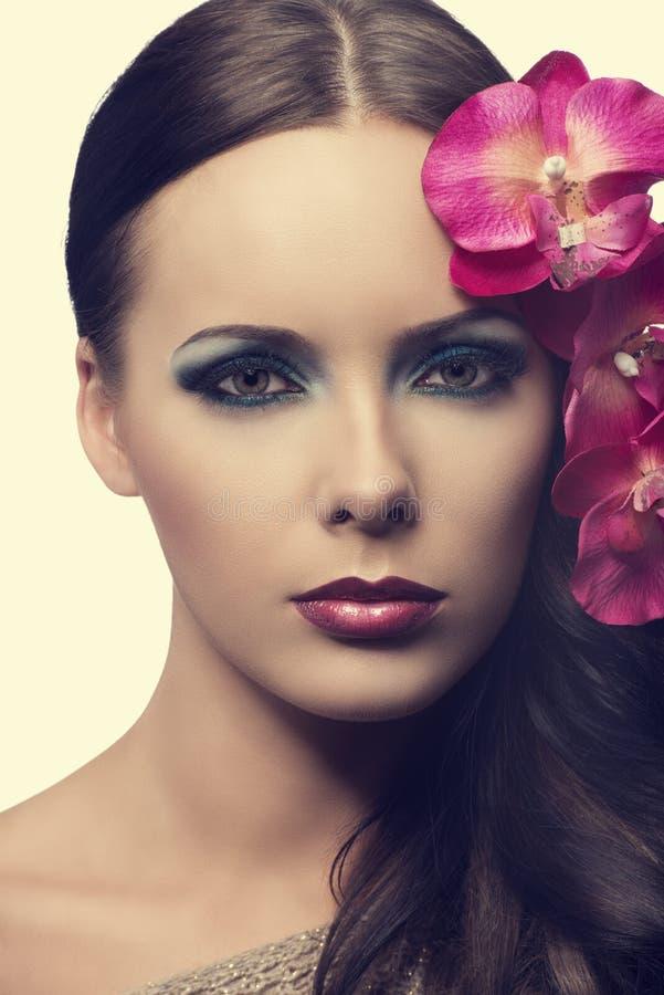 Chiuda su della ragazza di bellezza con i fiori. SIMULI I FIORI fotografia stock libera da diritti