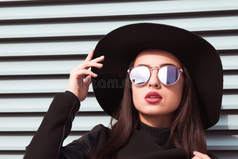 Il ritratto del primo piano di giovane modello seducente indossa il cappello e i sunglass immagine stock libera da diritti