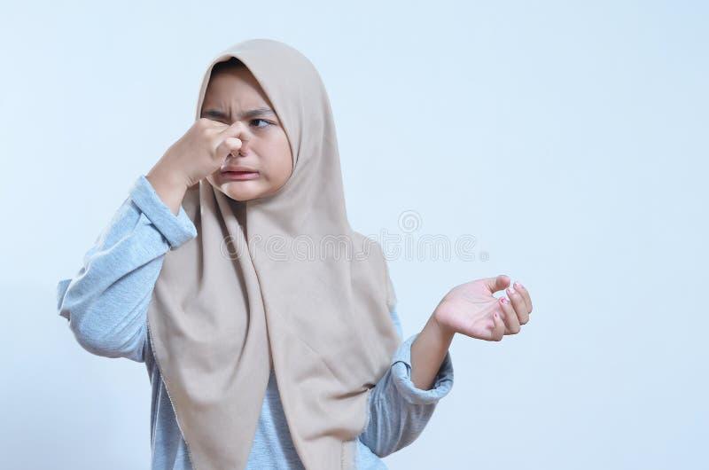 Il ritratto del primo piano di giovane naso asiatico della tenuta della donna si è chiuso a causa di cattivo odore fotografia stock libera da diritti