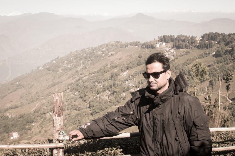 Il ritratto del primo piano di un uomo bello asiatico alla moda in vestiti dell'inverno, sta lateralmente su una montagna della n fotografia stock