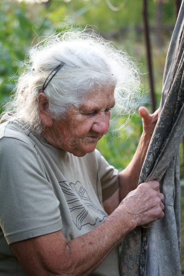 Il ritratto del primo piano di una donna anziana con capelli grigi appende i vestiti per asciugarsi su un fondo vago di un prato  fotografia stock libera da diritti