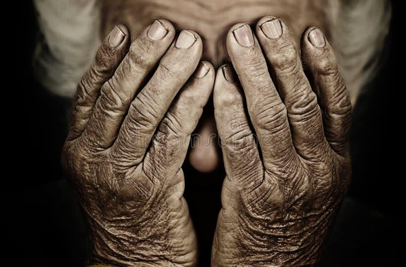 Il ritratto del primo piano ha depresso la donna anziana che copre il suo fronte di mano fotografia stock