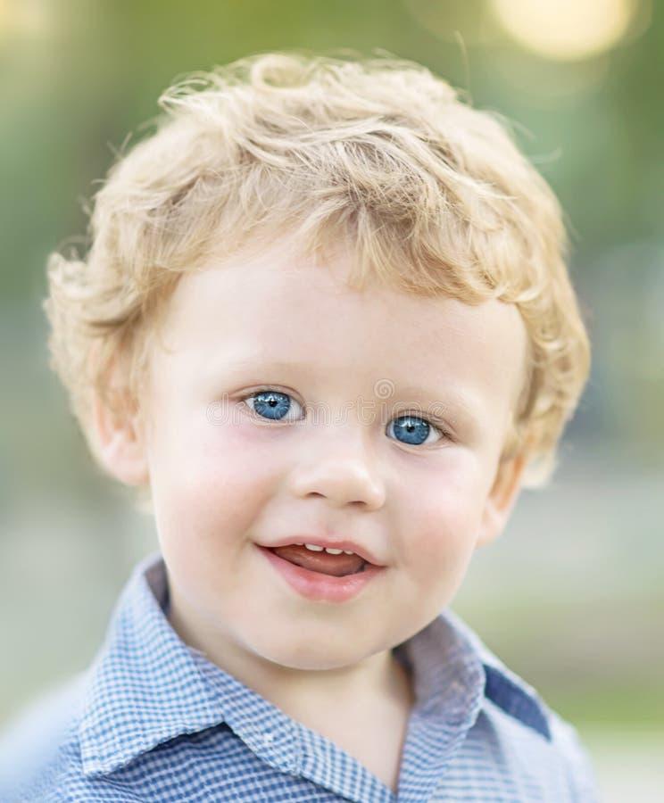 Il ritratto del primo piano del neonato sorridente felice sveglio in camicia blu su verde ha offuscato il fondo Piccoli 1,5 anni  fotografie stock