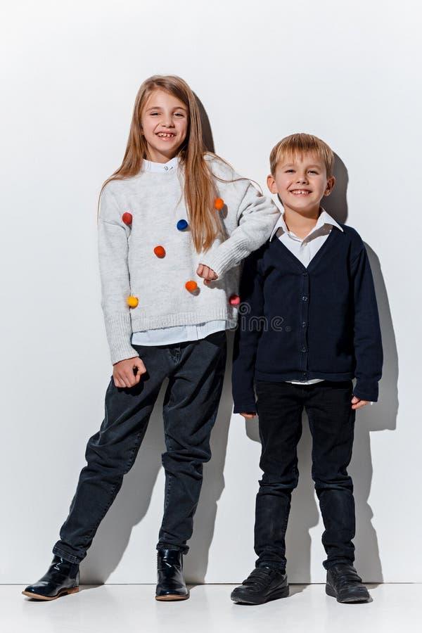 Il ritratto del ragazzino e della ragazza svegli in vestiti alla moda dei jeans che esaminano macchina fotografica lo studio immagini stock