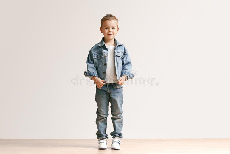Il ritratto del ragazzino sveglio in vestiti alla moda dei jeans che esaminano macchina fotografica lo studio fotografie stock