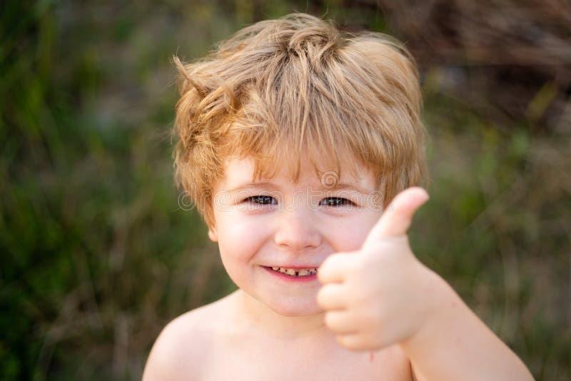 Il ritratto del ragazzo felice che mostra i pollici aumenta il gesto Bambino sul fondo di verde della natura Vacanze estive fotografia stock