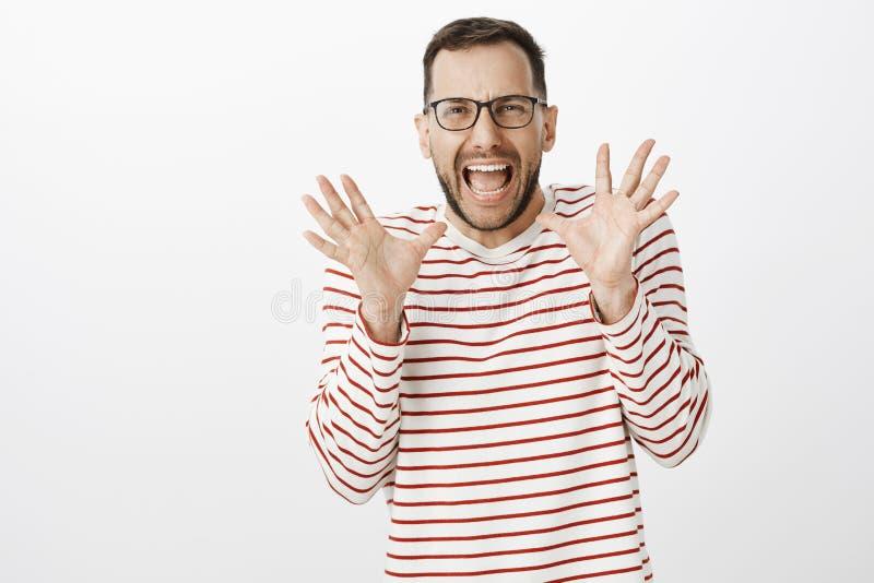 Il ritratto del ragazzo gay adulto spaventato sveglio in vetri, gridante dal timore e tenente le palme si è alzato vicino al fron fotografia stock