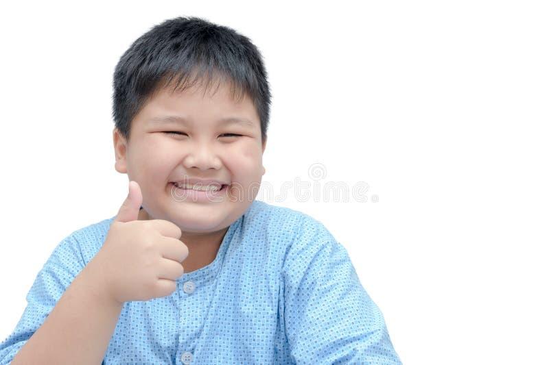 Il ritratto del ragazzo grasso felice asiatico che mostra i pollici aumenta il gesto fotografia stock libera da diritti