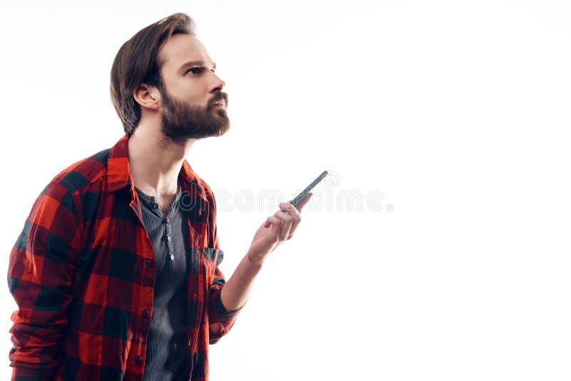 Il ritratto del telefono pensieroso della tenuta dell'uomo e cerca immagini stock