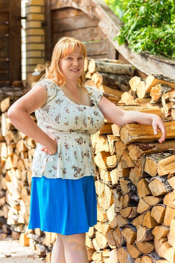Il ritratto dell'donne si avvicina alla catasta di legna fotografia stock libera da diritti