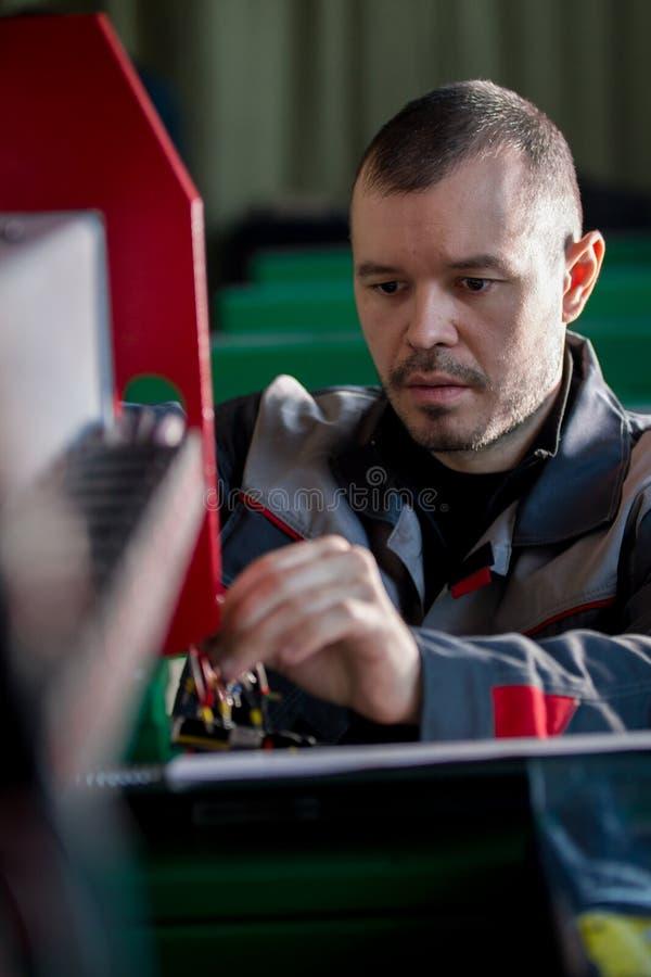 Il ritratto dell'elettricista sui camici sta funzionando con il pannello di energia e l'attrezzatura del macchinario sulla pianta immagini stock libere da diritti