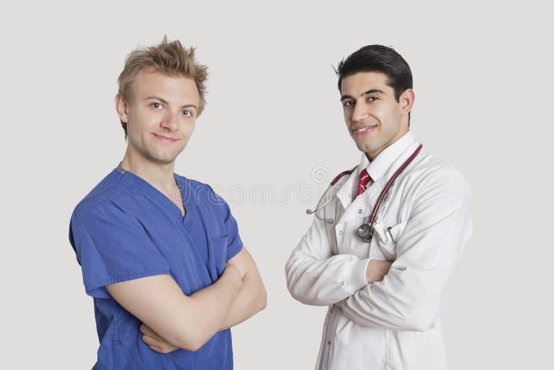 Il ritratto dell'infermiere felice e di medico maschii che stanno con le armi ha attraversato il fondo grigio fotografia stock libera da diritti