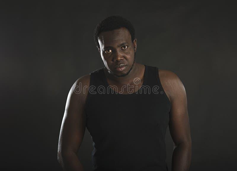 Il ritratto dell'uomo afroamericano ben fatto che sta sul nero ha isolato il fondo fotografia stock